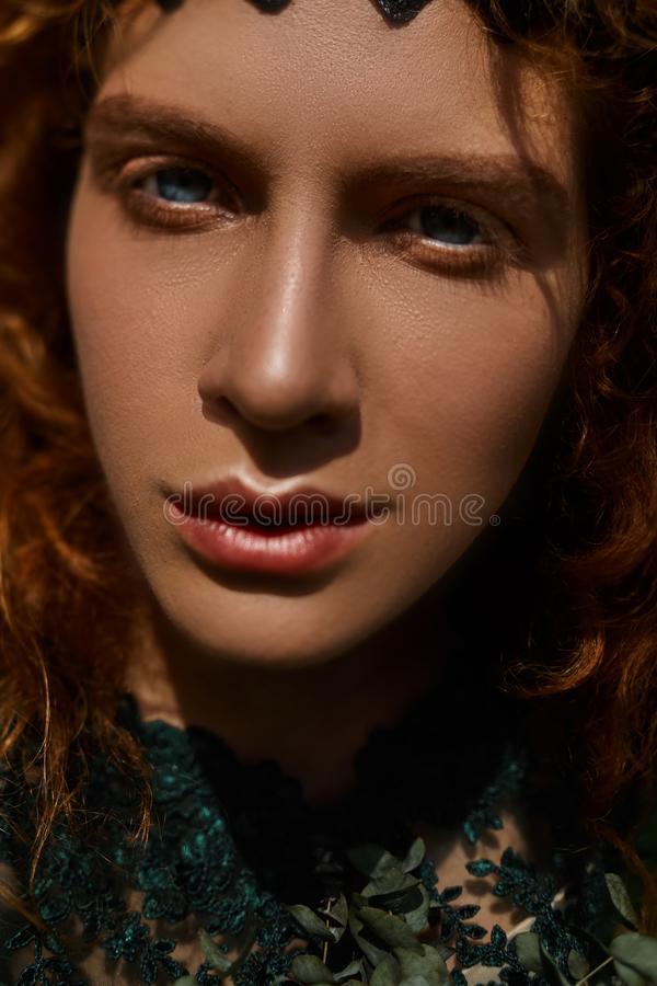 Close up portrait of a beautiful redhead girl playing with hair royalty free stock image