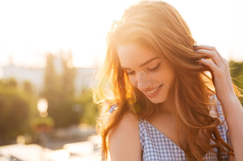 Close up portrait of a redhead girl playing with hair royalty free stock photo