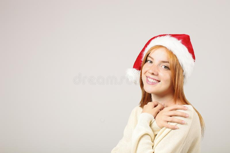 Close up portrait of beautiful redheaded young woman wearing Santa Claus hat & white sweater with satisfied facial expression. Cut royalty free stock images