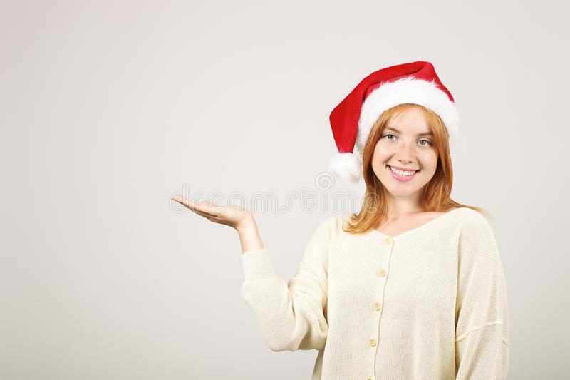 Gorgeous redhead female wearing Santa`s hat with pop-pom, celebrating winter festive season holidays. stock images