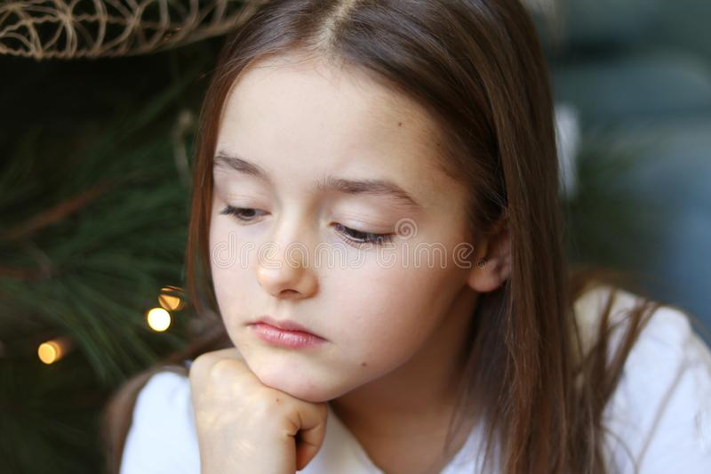 Close up portrait of beautiful sad little girl sitting under decorated Christmas tree thinking stock photos