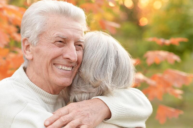 Portrait of beautiful senior couple embracing in the park royalty free stock photo