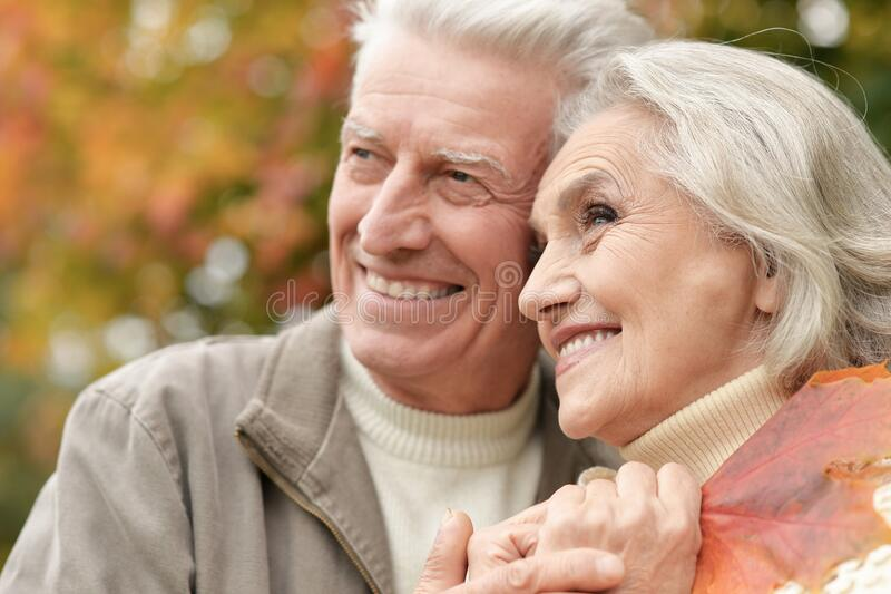 Portrait of beautiful senior couple with leaves in the park stock image