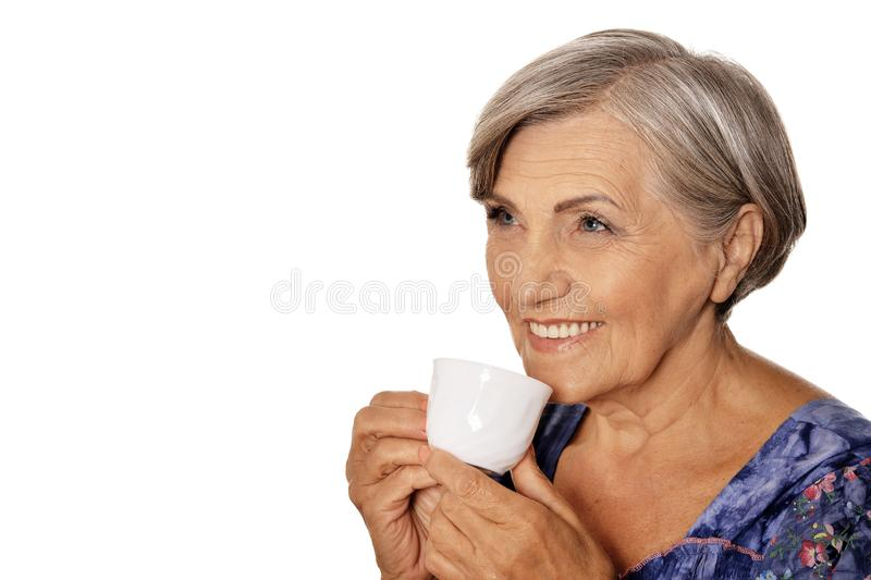 Close up portrait of beautiful senior woman with cup isolated on white background stock photography
