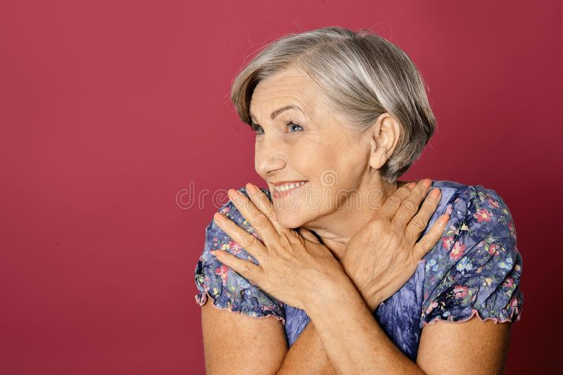 Close up portrait of beautiful senior woman  on red background royalty free stock photos