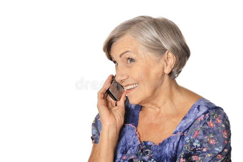 Close up portrait of beautiful senior woman talking on phone isolated on white background stock photography