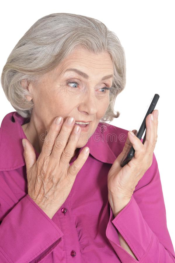 Close up portrait of beautiful senior woman talking with smartphone on white background royalty free stock photography