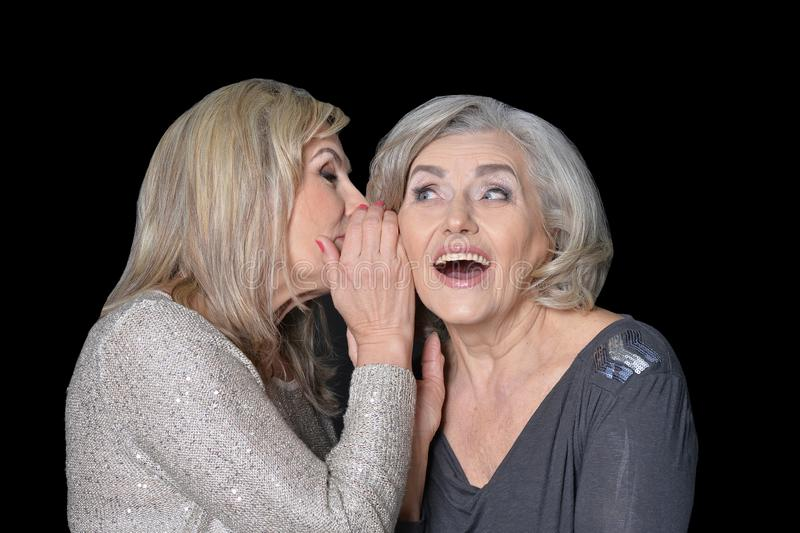 Close up portrait of beautiful senior women sharing secret stock image