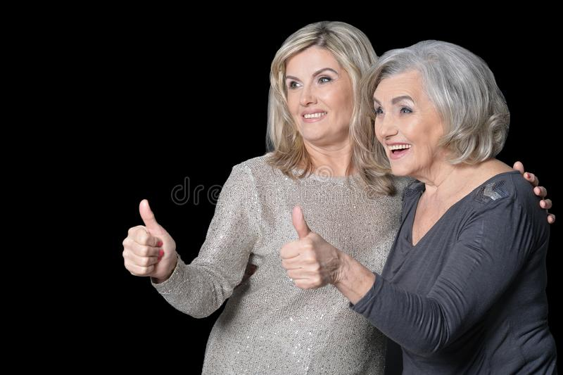 Close up portrait of beautiful senior women with thumbs up stock photo