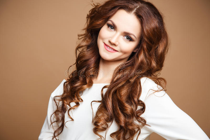 Close-up portrait of beautiful young woman with long brown hair over brown background stock photos