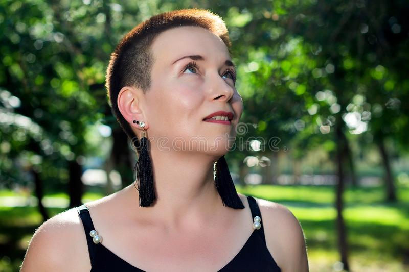 Close-up portrait of a beautiful short-haired woman in the park stock photos