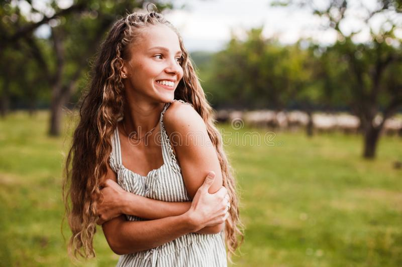 Close-up portrait of a beautiful smiling blonde girl with natural curls. stock images