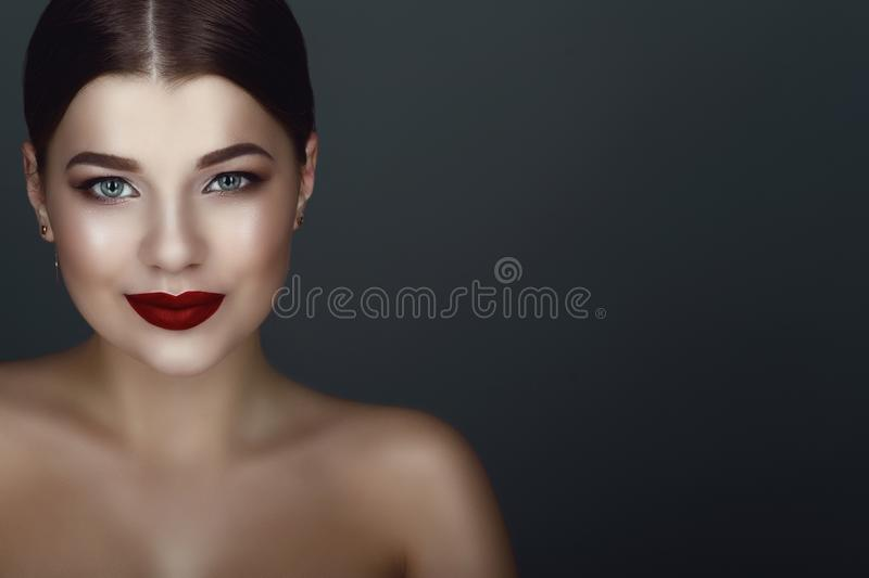 Close up portrait of beautiful smiling dark-haired model with perfect make up and centre part sleek bun stock photography