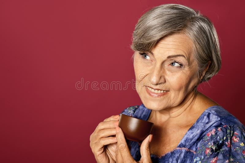 Close up portrait of beautiful smiling senior woman drinking tea stock image