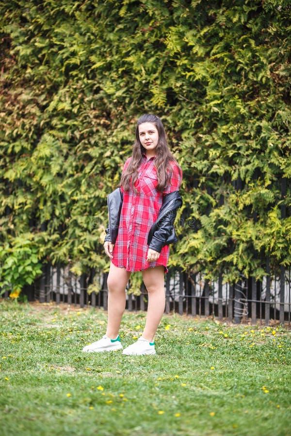 Close up portrait of beautiful stylish plus size model kid girl in plaid shirt and leather jacket.  stock photo