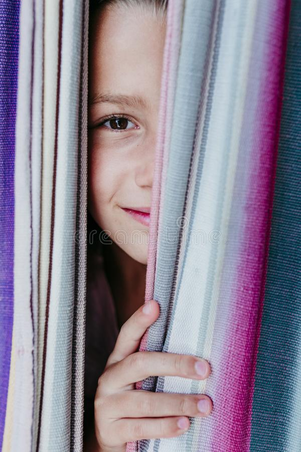 Close up portrait of beautiful teenager girl lying on colorful hammock at the garden. Looking at the camera and smiling. LIfestyle royalty free stock photos