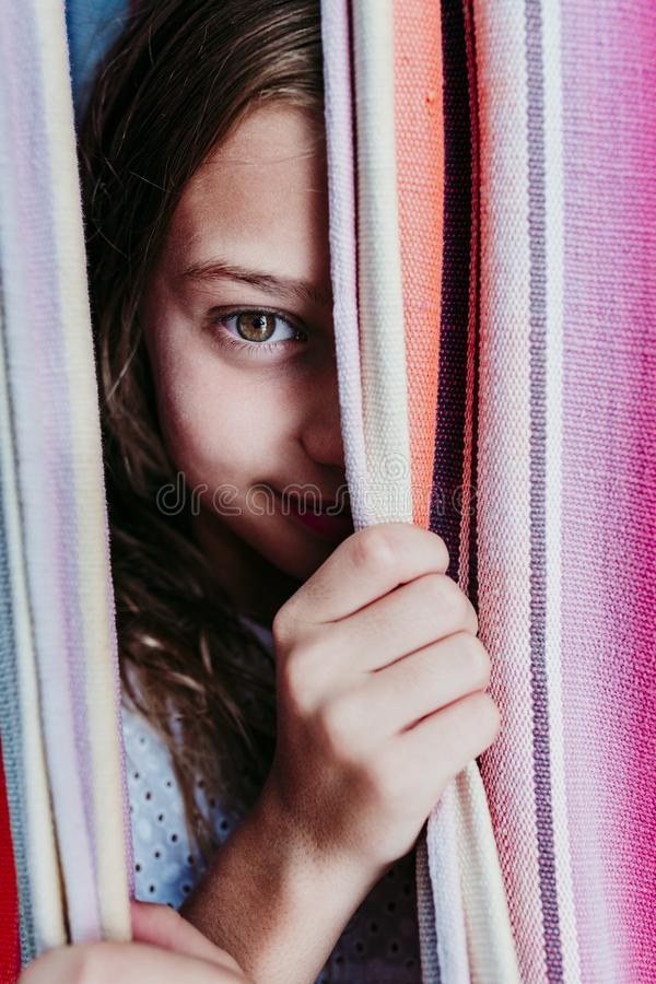 Close up portrait of beautiful teenager girl lying on colorful hammock at the garden. Looking at the camera and smiling. LIfestyle. Relax and fun outdoors stock photos