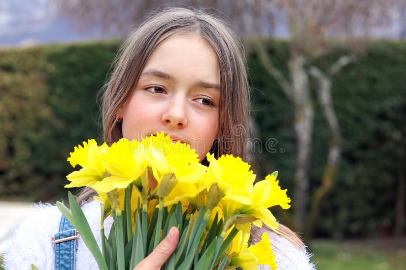 Close up portrait of beautiful tween romantic girl holding bouquet of bright yellow spring daffodil flowers at her face hugging it stock photography