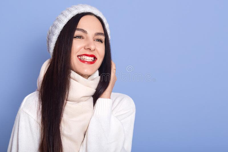 Close up portrait of beautiful winter woman in warm clothing, lady looking aside with charming smile, dresses white sweater, stock photo