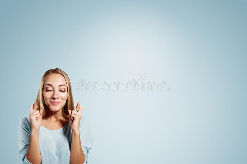Close-up portrait of a beautiful woman closing her. Eyes, crossing her fingers hoping for the best,isolated on blue background royalty free stock photos