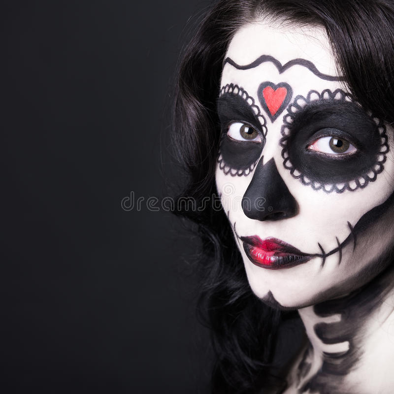 Close up portrait of beautiful woman with creative sugar skull m. Ake up over black background stock images