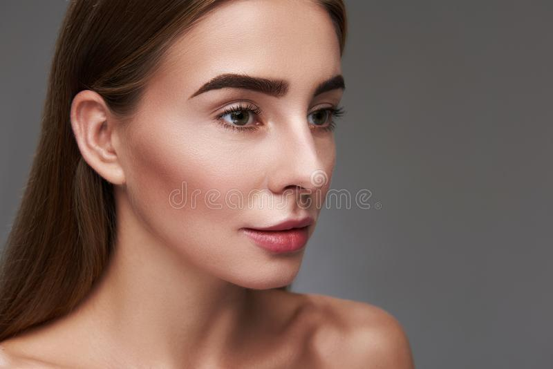 Charming young lady with natural makeup isolated on gray background royalty free stock photo