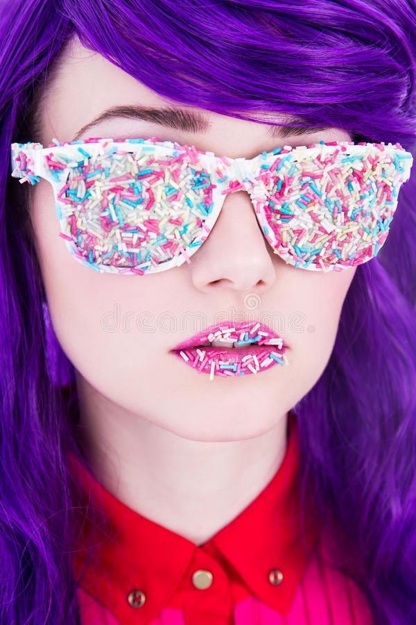 Close up portrait of beautiful woman with purple hair and glasses covered by colorful sugar candies. Close up portrait of young beautiful woman with purple hair royalty free stock photography