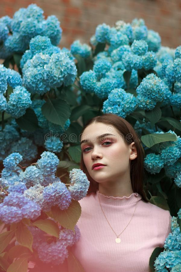 Close up portrait of the beautiful young brunette girl with bright makeup wearing pink t-shirt standing among blue royalty free stock photo