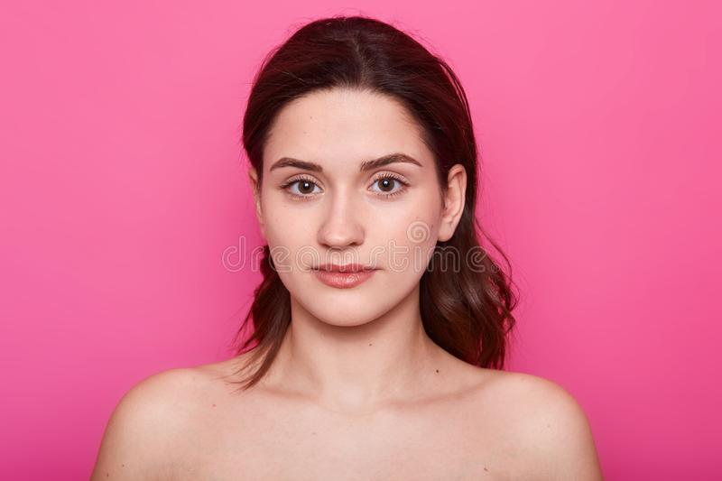 Close up portrait of beautiful young caucasian brunette woman with clean skin after procedures in spa salon, shows bare shoulders royalty free stock photography