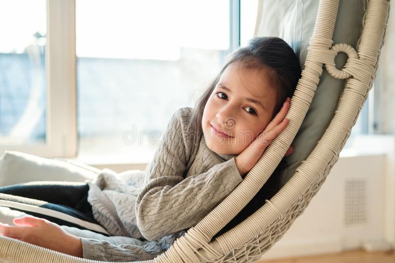 Close up portrait of beautiful young child girl lying at handing chair. Kid relaxing in cozy home stock photography
