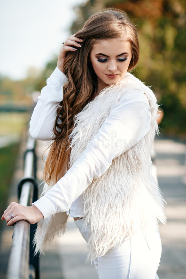 Close-up portrait of a beautiful young confident girl or businesswoman in a white suit with a beautiful make-up and hairdo on. The waterfront stock photography