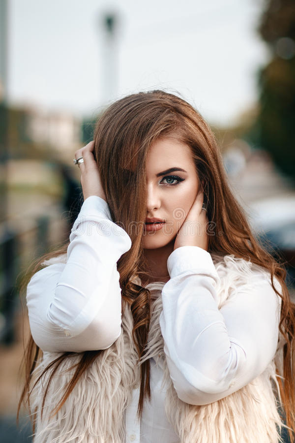 Close-up portrait of a beautiful young confident girl or businesswoman in a white suit with a beautiful make-up and hairdo on royalty free stock photo