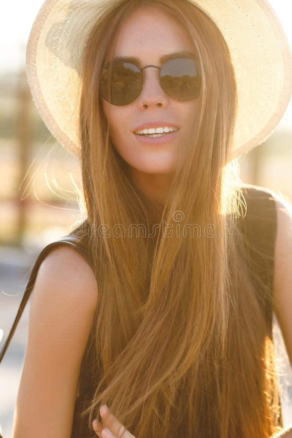 Close-up portrait of a beautiful young girl with long dark hair wearing straw hat, dark sunglasses. She plays with her stock images