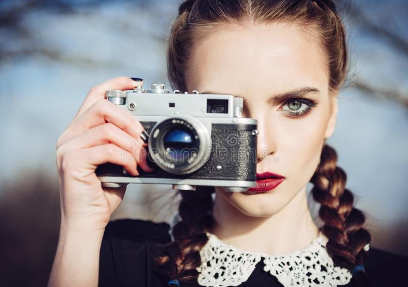Close-up portrait of beautiful young girl with old film camera in hand stock photography