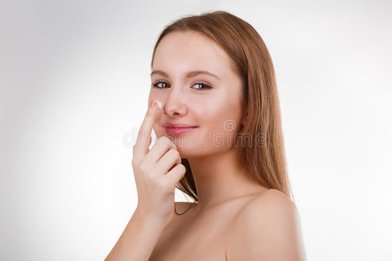 Close up portrait of beautiful young happy smiling girl applying cream on her nose royalty free stock images