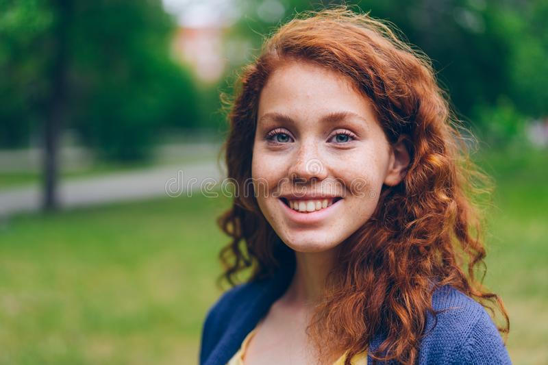Close-up portrait of beautiful young lady smiling at camera in park in summer stock image