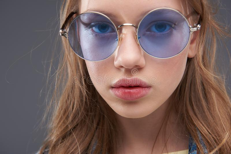 Charming teenage girl wearing blue round glasses. Close up portrait of beautiful young lady in stylish eyeglasses looking at camera with serious expression royalty free stock image
