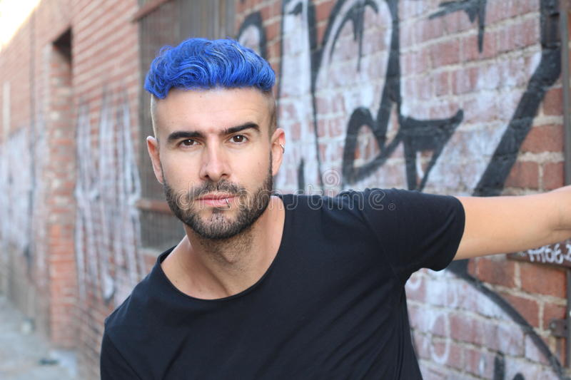 Close-up portrait of a beautiful young man with blue hair. Men's beauty, fashion. stock photos
