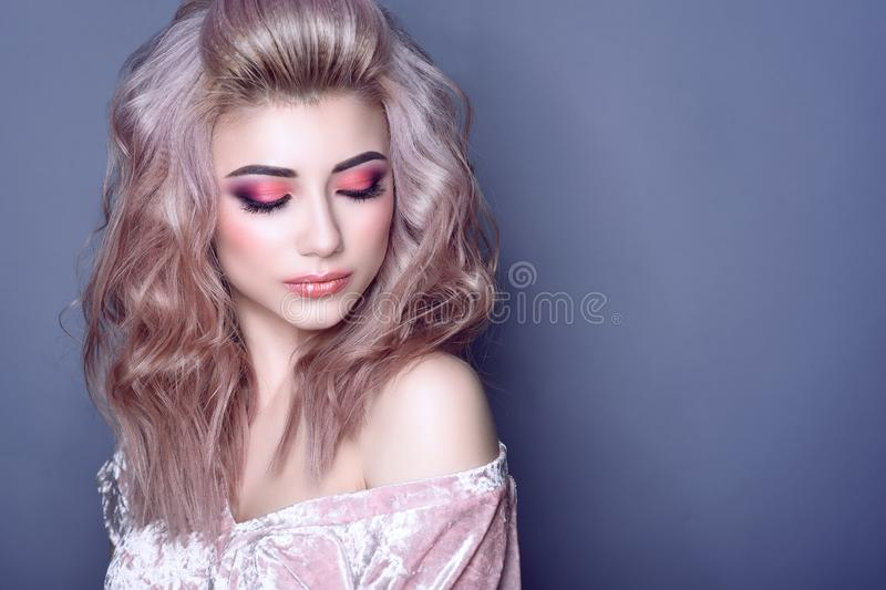 Beautiful young model with colorful artistic make up and wavy hairstyle looking down royalty free stock photo