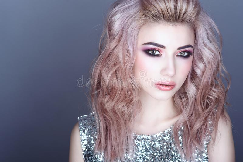 Beautiful young model with colorful artistic make up and wavy hairstyle wearing silver sequin top royalty free stock image