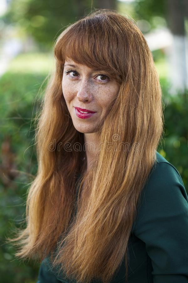 Beautiful young red hair woman posing on summer park. Close up portrait beautiful young red hair woman posing on summer park stock photo