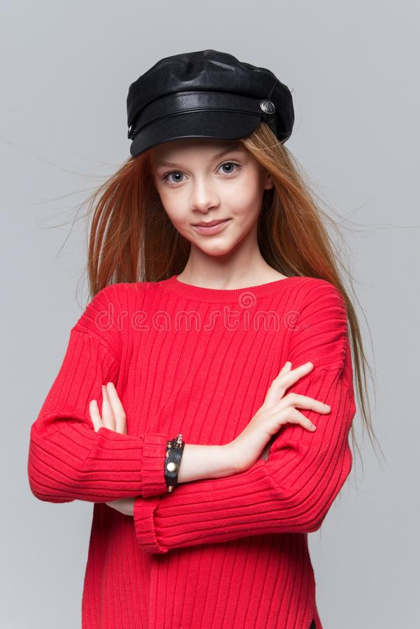 Close-up portrait of beautiful young redhead girl wearing red sweater posing in studio. stock photography