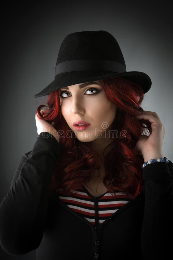 Close up portrait of a beautiful young redhead woman. Posing with a black fedora hat in the studio royalty free stock photos