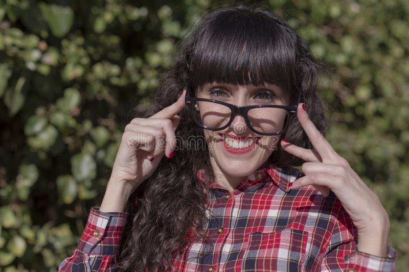 close up portrait of a beautiful young woman adjusting glasses and looking at the camera smiling. Fun and lifestyle royalty free stock image