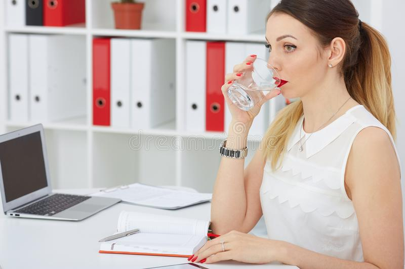 Close up portrait of a beautiful young woman drinking water at work place. stock images