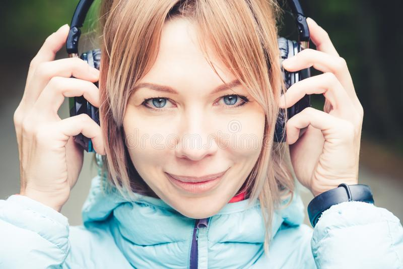 Close up Portrait of a beautiful young woman holding headphones listening to music outdoors in the forest. Joyful music royalty free stock photography