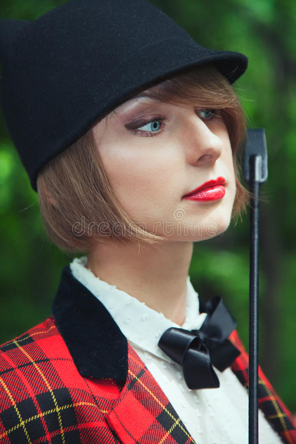 Close-up portrait of beautiful young woman in horsewoman suit in stock image