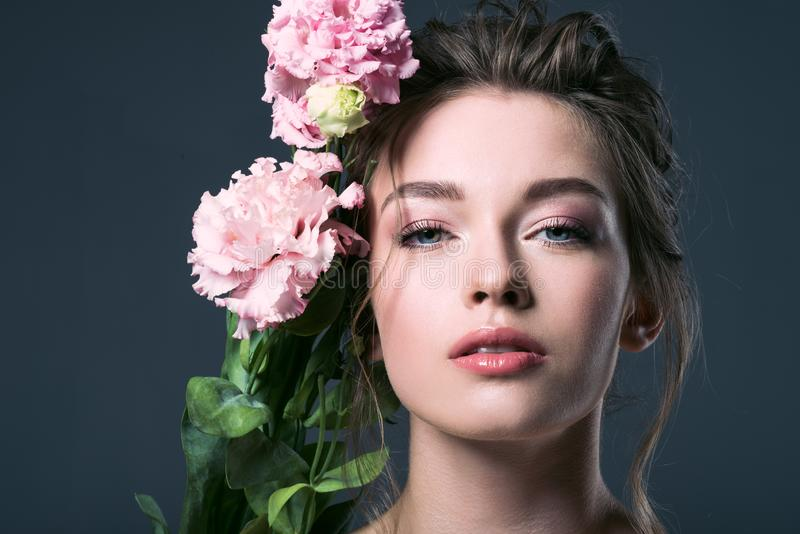 close-up portrait of beautiful young woman with pink eustoma flowers behind ear looking at camera stock image