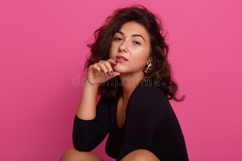 Close up portrait of beautiful young woman thinking about something important, keeps hand under chin, looks at camera, isolated royalty free stock photography