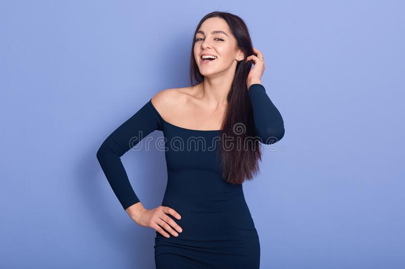 Close up portrait of beautiful young woman waring dress, standing and looking at camera isolated over blue background, fells happy royalty free stock images